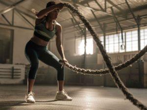 femme lors d'un entrainement de crossfit réalisant un Battle rope